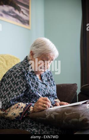 Senior woman doing crossword puzzle at home - Stockfoto