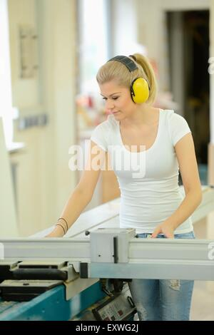 Young woman working in a carpentry on a buzzsaw - Stockfoto