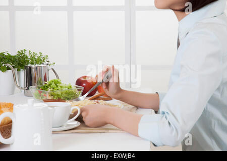 Young woman eating breakfast on the table, - Stock Photo