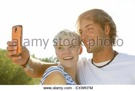 Happy young couple outdoors taking a selfie - Stock Photo
