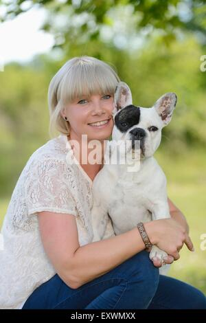 Woman with a seven month old French Bulldog - Stock Photo