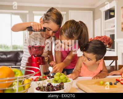 Kinder (2-3, 6-7, 8-9) Vorbereitung Fruchtcocktails - Stockfoto
