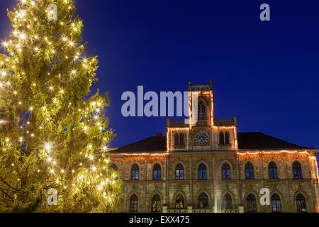 Illuminated Christmas tree and building facade - Stock Photo