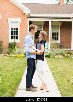 Young couple standing on footpath in front of house - Stock Photo