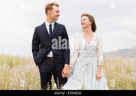 Newlywed couple in field - Stock Photo