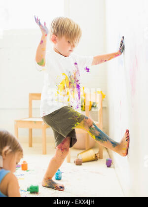 Boy (2-3) painting on wall with hands and legs - Stock Photo