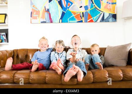 Smiling children (2-3, 4-5, 6-7) sitting on sofa - Stockfoto