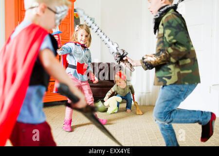 Children (2-3, 4-5, 6-7) wearing superhero costumes playing at home - Stockfoto