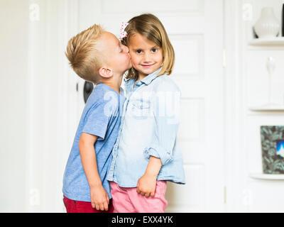 Little boy (4-5) kissing sister (4-5) - Stock Photo