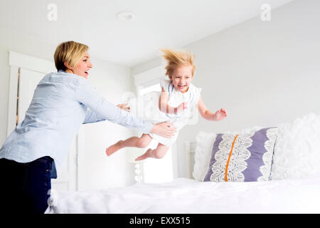 Woman playing with girl (2-3) in bedroom - Stock Photo