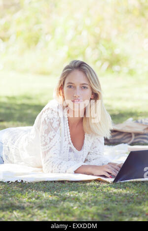 College student using laptop outdoors - Stockfoto