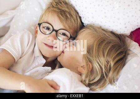 Little girl kissing big brother - Stock Photo