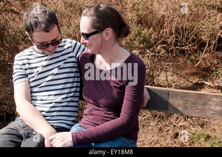 Couple with their arms around each other sitting on a bench - Stockfoto