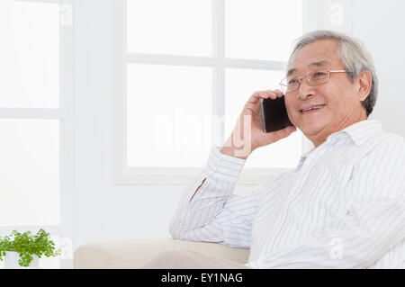 Senior man using mobile phone and looking away with smile, - Stock Photo