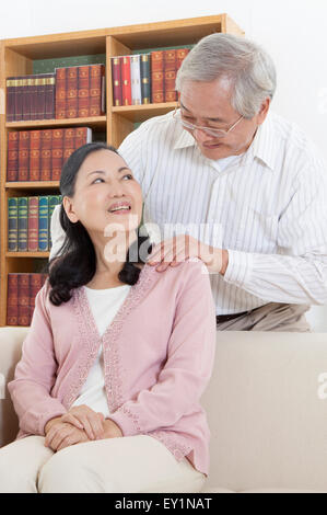 Senior man smiling at senior woman with hands on shoulder, - Stock Photo