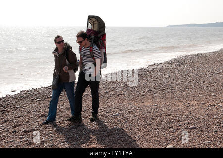 Couple out for a walk with their baby asleep in a baby carrier - Stock Photo