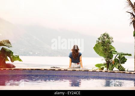 Young woman sitting on edge of pool, San Pedro, Lake Atitlan, Guatemala - Stock Photo