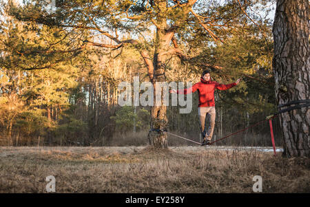 Young man balancing on slackline in forest - Stock Photo