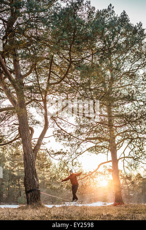 Young man balancing on slackline in lakeside forest - Stock Photo
