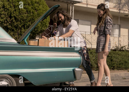 Young couple packing vintage car boot for road trip - Stock Photo