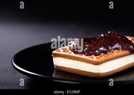 Ice cream sandwich with Strawberry jam on a dark plate - Stock Photo