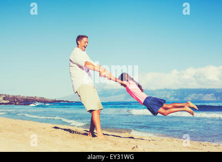 Happy father and daughter playing together at the beach. Fun vacation summer lifestyle. - Stock Photo