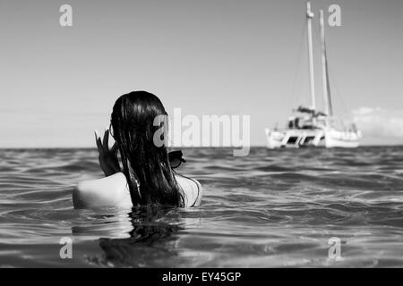 A girl removes her sunglasses and rubs her eyes after emerging from a swim in the ocean, looking at a catamaran - Stock Photo