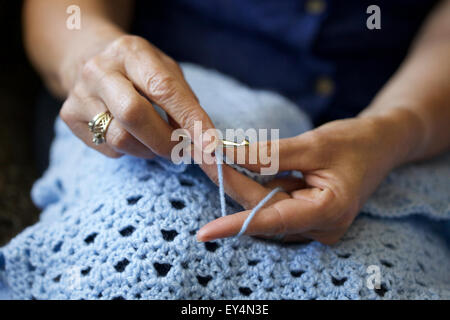 Close up picture of a Caucasian woman crocheting at home - Stock Photo