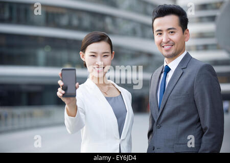 Business person showing smart phone - Stock Photo