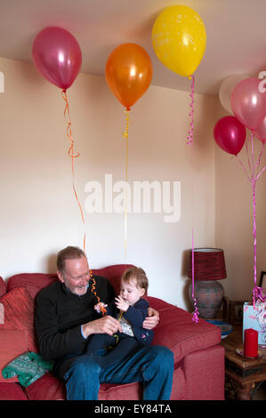 Baby girl sitting on her grandfathers lap playing with a balloon - Stockfoto