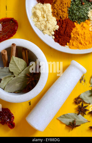 Colorful cooking spices and herbs on a round plate with cinnamon sticks, bay leaves and star anise in mortar and - Stock Photo