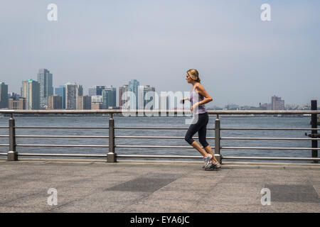 Woman running, jogging at Hudson river park.  Manhattan, Jersey city in background. NYC. USA. - Stock Photo