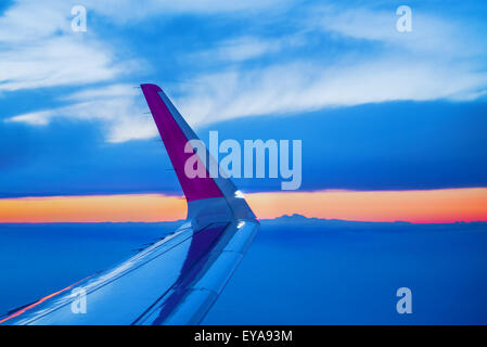 Airplane Wing Seen Through Open Porthole Window During the Flight of Commercial Passenger Aircraft, Sunset on Horizon - Stock Photo