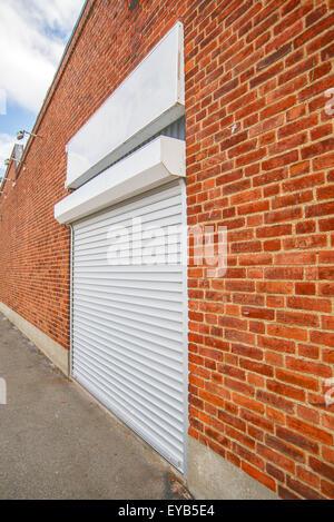 Industrial Roll Shutter Garage Door, Brick Wall, Urban Setting - Stock Photo