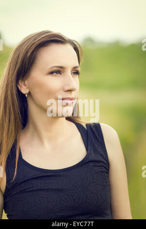 Young smiling fitness woman wearing tight sportswear at outdoor. Pretty sport girl looking aside with copy space - Stock Photo