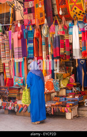 Morocco, Marrakesh, woman in traditional cloth in front of a shop - Stock Photo