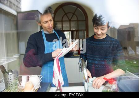 View through window of teenage boy and father washing up in kitchen - Stock Photo