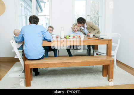 Family at breakfast table in kitchen - Stock Photo