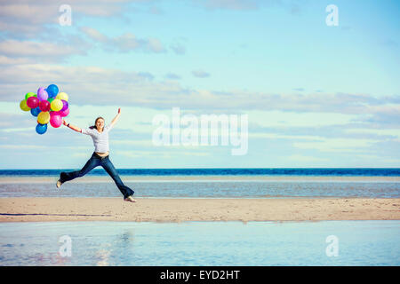 Beautiful girl jumps on the beach while holding colored balloons - Stock Photo