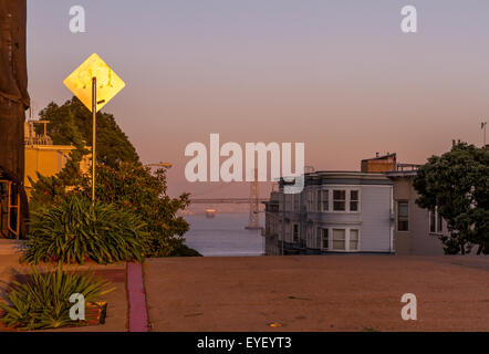 Oakland Bay Bridge from The top of a steep Hill in North Beach ,San Francisco California at Sunset - Stock Photo