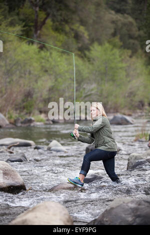 Young woman fly fishing with mountains in the background ...