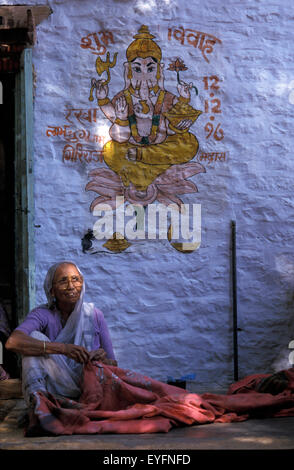 Woman sewing by blue wall with painting of ganesh; Jaisalmer, Rajasthan, India - Stockfoto