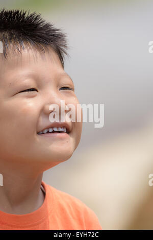 Portrait of a little mongoloid boy happy and smiling with copy space - Stock Photo