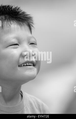Black and white Portrait of a little mongoloid boy happy and smiling with copy space - Stock Photo