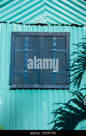 Flic en Flac, Mauritius. Closed blue shutters on a tourquoise corrugated wall with palm leaf shadow. - Stock Photo
