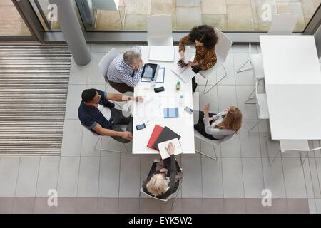 Overhead view of business team having meeting at conference table - Stock Photo