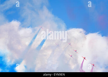Royal Air Force Red Arrows obscured by vapour trails after passing overhead during an airshow display - Stock Photo