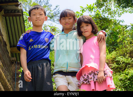 Three young children standing together with copy space - Stock Photo