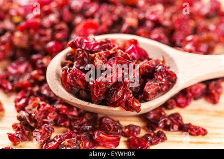 Dry red barberry spices in the wooden spoons - Stock Photo