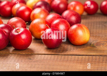 Sweet plums on wooden background - Stockfoto